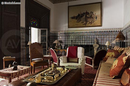 Moroccan living room with original wall tiling and red and ivory striped sofa in 20th century riyad in the medina of Marrakesh with interior restoration by Jean-Louis Raynaud and Kenyon Kramer