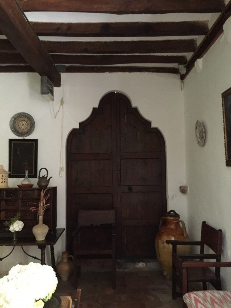 Spectacularly shaped door opening in this charming sitting room filled with the expected Spanish furnishings.
