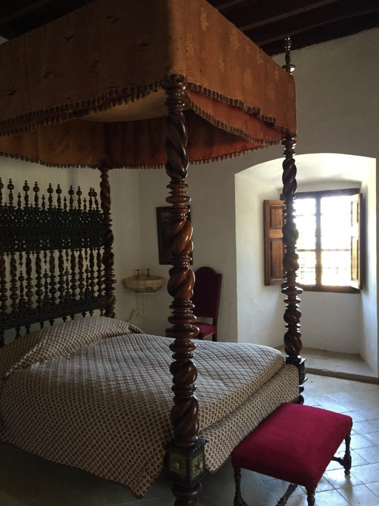 Sparsely decorated bedroom on display with its gorgeous Portuguese-style poster bed.