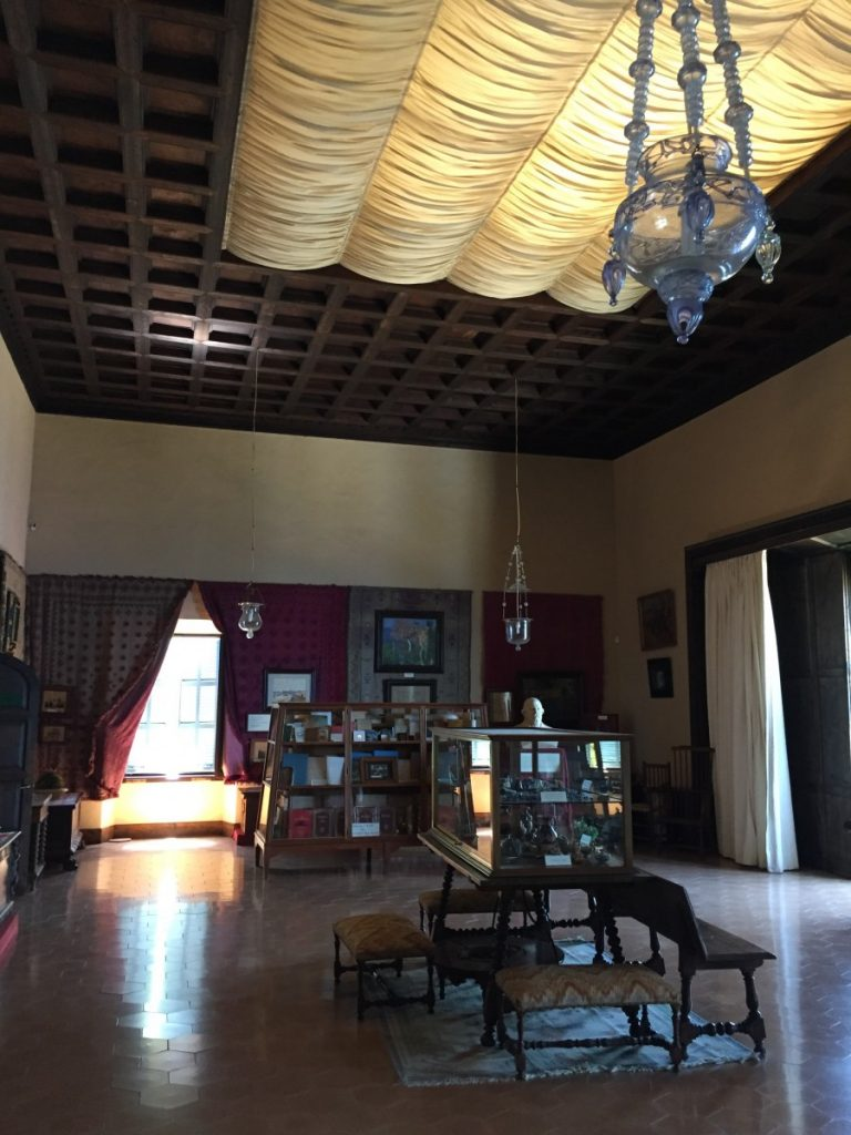 The upstairs salon with its heavywooden ceiling, tiled floors, and charming glass pendants.