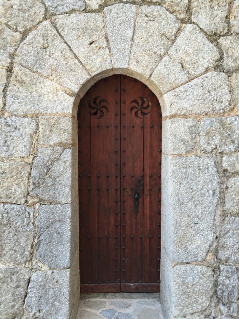 Charming door with clavos and pinwheel cutouts.