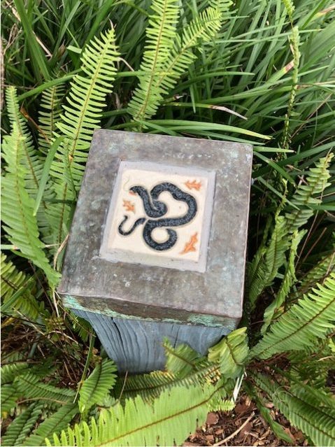A cute snake tile is tucked into a bed of ferns, Bok Tower and Gardens.