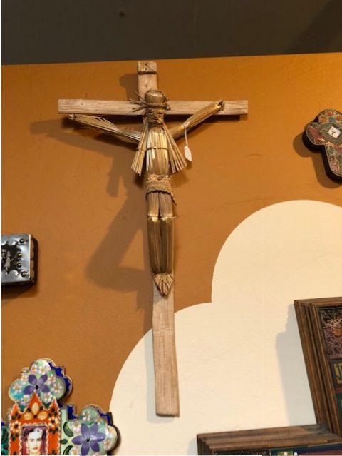 A charming humble straw and wood crucifix on a wall of many, Arte de la Vida.