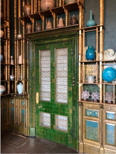 Chinese lattice fills the openings of the malachite-colored doors.