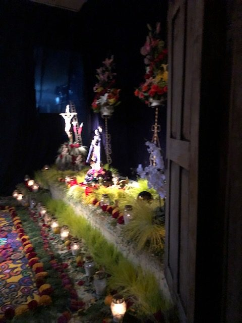 A home altar featuring yellow and purple flowers along with spring grass. Each has a special meaning.