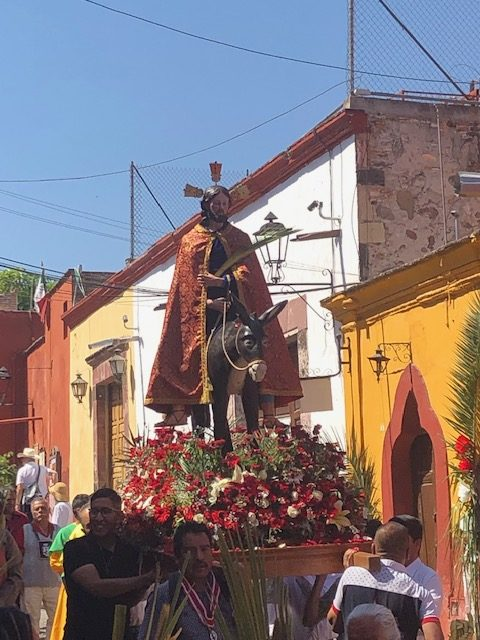 The highlight of the procession was Jesus atop a donkey surrounded by red and white flowers symbolizing happiness.
